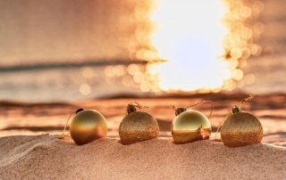 Gold ornaments sit on the beach, decorating the sands against the background sunset to commerate a Florida Gulf Coast holiday.